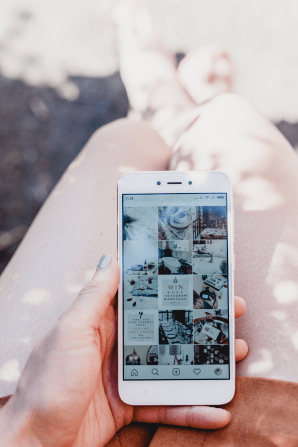 Girl holding phone with Instagram app open. Instagram is a real thing affecting many users.