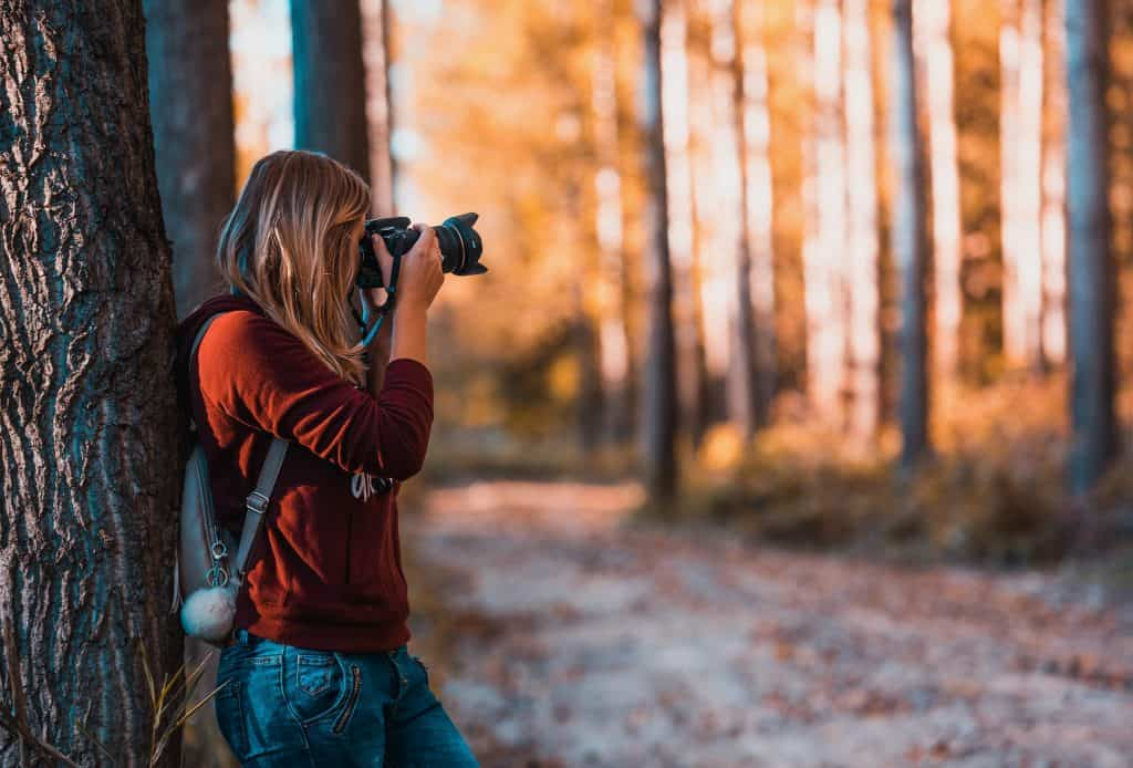 A woman taking a picture in an autumn wood.