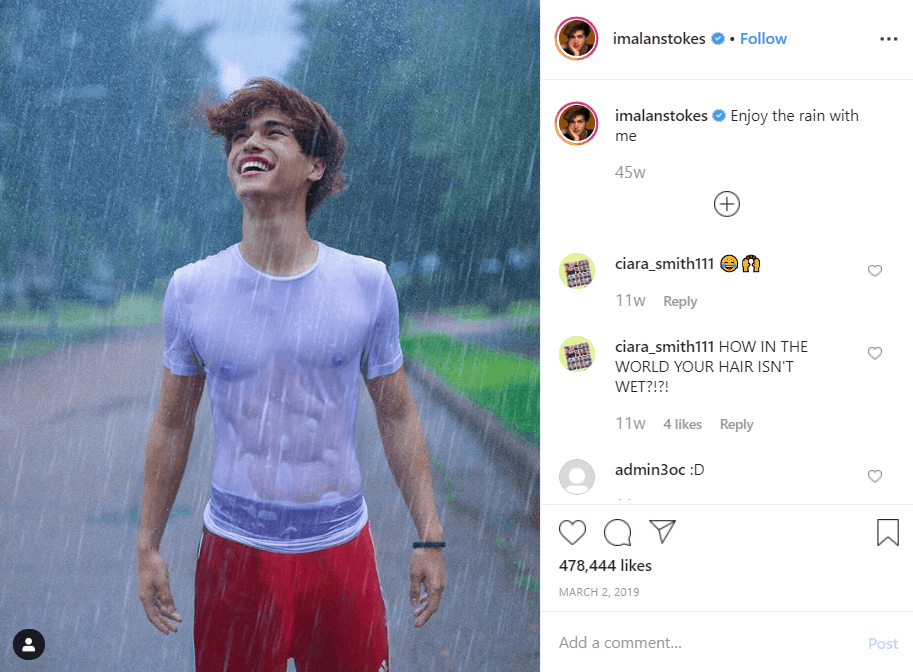 Boy standing in the rain with wet clothes but dry hair