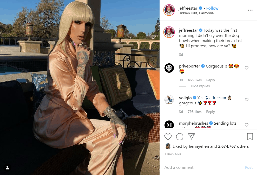 Jeffree Star posing in the sunlight in a pink outfit and blonde wig