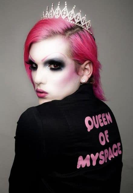 Jeffree Star with pale skin, dark eyeshadow, pink wig and sweater that says Queen of MySpace